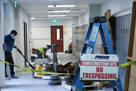 Construction workers remove debris and lay tile in the hallway that connects the 1300 and 1400 hallways. Construction around the school is expected to be complete by the end of the summer.
