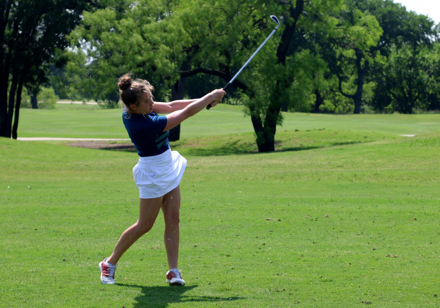 Senior Gracie Tribolet follows through after hitting the golf ball at a practice prior to the state tournament. This year was Tribolet's fourth year on the golf team