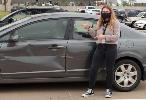 Senior Jacquelyn Burrer poses next to her car. The dent in her car was a result of an accident where she got T-boned on Marsh and Plano Parkway.