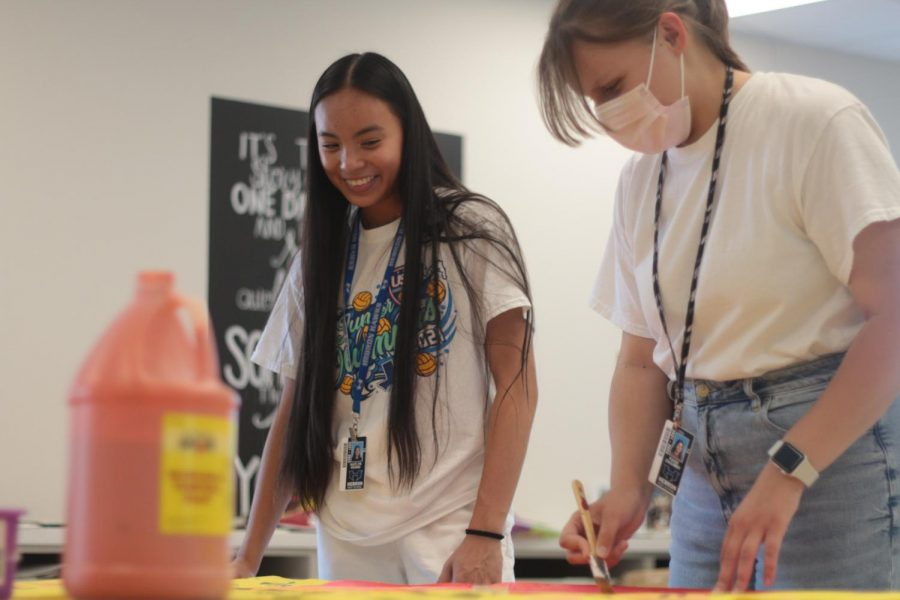 Student Council senior officer Kaitlyn Hoang and President Paige Zagumny paint a poster to promote Senior Sunrise during their third period student council class. Zagumny and the other officers spend their class period organizing, preparing and advertising school events.