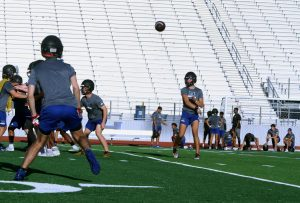 Quarterback Braxton Baker passes the ball to his teammate during practice before school on Aug. 25. The team practiced a variety of new plays in preparation for the upcoming game against Guyer in hopes to defeat them, unlike last year.