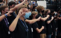"""The HawkAppella choir closes out the pep rally by leading the crowd in the school song. """"This was my first time performing in a pep rally,"""" junior Christopher Clausen said. """"It was very exciting to go down to the court and sing a song for most of the school. At first I was a bit nervous, but since I was singing with my friend it was fun and enjoyable. I got a chance to sing in front of my classmates that didn't go to our concerts and was happy that they got to hear us."""""""