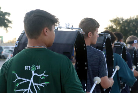 Junior Jack Rossi practices with the drumline before school on Sept. 17. Rossi plays Bass 5, the largest bass drum, and is also the co-leader of the band's media team.