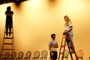 """Junior Kyler Beck stands on a ladder and observes while senior Kaamil Thobani and junior Emma Foughty rehearse a scene in Act 1 of """"Our Town."""" The play is unique in the sense that it does not use a traditional set or props — in this scene, the actors on ladders are implied to be 'upstairs' in their respective homes."""