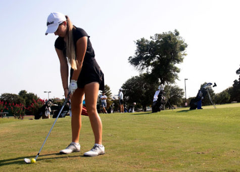 Senior Nina Gudgeon lines up the ball before she swings. With the golf tournament season starting, all of the golf teams have been preparing for upcoming competitions.
